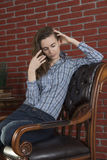 Young woman sits in a chair Royalty Free Stock Photo