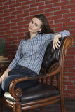 Young woman sits in a chair Royalty Free Stock Photos