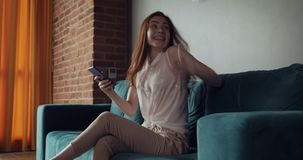 Young woman sits on the couch and using smartphone. stock video footage