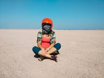 Young woman sits in the desert wearing a helmet for buggy. Young woman sits alone in the middle of the desert wearing a helmet for buggy Royalty Free Stock Image