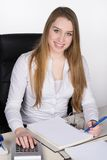 Young woman sits at the desk Stock Photography