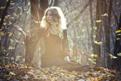 Young woman sits in the fairy wood stock image