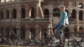 Young woman sits on fence against background of Colosseum in Rome, Italy in sunny day. Female swings legs. Slow motion. stock footage