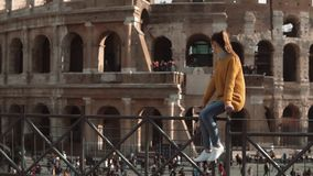 Young woman sits on fence looking at Roman Colosseum in Italy. Girl enjoys the vacation in Rome. Slow motion. stock video
