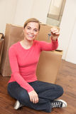 Young woman sits on the floor holding a key in her Stock Image
