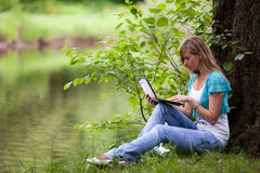 Young woman sits on a grass in park. Royalty Free Stock Images
