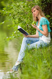 Young woman sits on a grass in park. Royalty Free Stock Image