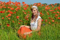 The young woman sits on a grass in a poppy field Stock Photo