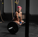 Young woman sits at gym with barbells on floor Royalty Free Stock Image