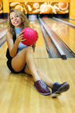 Young woman sits and holds ball in bowling club Stock Photo
