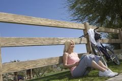 Young Woman Sits Leaning Against Fence Royalty Free Stock Photo