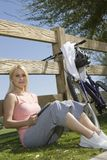 Young Woman Sits Leaning Against Fence Stock Images