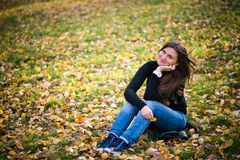 Young woman sits on leaves Royalty Free Stock Image