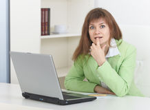 Young woman sits at light office with laptop Stock Images