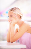 Young woman sits at little table at restaurant Stock Photography