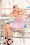 Young woman sits at little table at restaurant Royalty Free Stock Photography