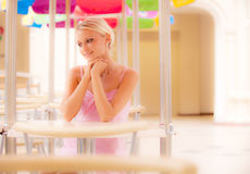 Young woman sits at little table at restaurant Royalty Free Stock Photos
