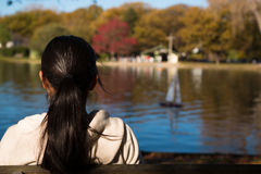 Young woman sits and looks at model yacht on a lake Stock Images