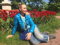 The young woman sits near the bright blossoming tulips Stock Photography