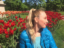 The young woman sits near the bright blossoming tulips Stock Images
