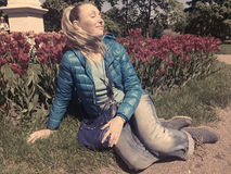 Young woman sits near the bright blossoming tulips , toning, retro effect Royalty Free Stock Photo