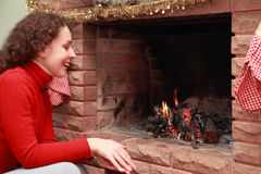 Young woman sits near fireplace Royalty Free Stock Image