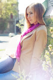 Young woman sits near a metal fence Royalty Free Stock Photo