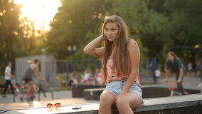 Young Woman Sits on Ramp In Skate Park and Flirting. In Slow Motion with Sun Flares stock video