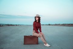 Young woman sits on retro suitcase Stock Images