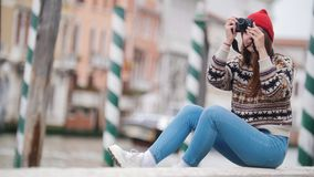 Young woman sits by the river and takes interesting photo. Mid shot stock video footage