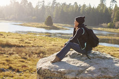 Young woman sits on a rock in countryside admiring the view Stock Photos
