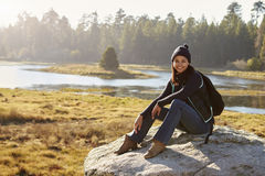 Young woman sits on a rock in countryside looking to camera Royalty Free Stock Image