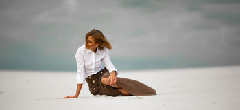 Young woman sits on sand in desert and pensively looks aside. Stock Photos