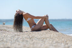 Young woman sits on seashore with eyes closed Royalty Free Stock Photography