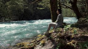 Young woman sits on the shore near the swift river stream she looks at the water. A young woman sits on an earthen bank near the swift river stream, a lady looks stock video footage