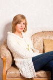 Young woman sits on a sofa Stock Image