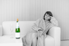 Young woman sits on sofa and looks at wine royalty free stock photography