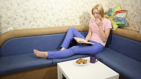 Young woman sits on a sofa, reads a book and drinks tea stock video