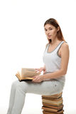 A young woman sits on a stack of books. Keeps the book on her lap. Royalty Free Stock Photos