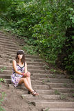 Young woman sits on a stairs Stock Photography