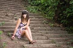 Young woman sits on a stairs Royalty Free Stock Images