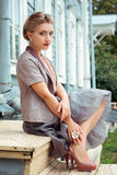 Young woman sits on steps of house Royalty Free Stock Photo