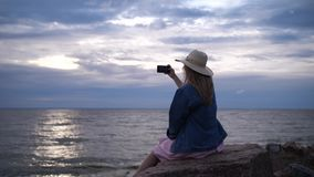 A young woman sits on a stone and takes a photo on the phone. The girl photographs the sunset sky. 4K Slow Mo stock footage