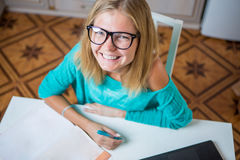 Young woman sits at the table with a laptop and paperwork Stock Photography