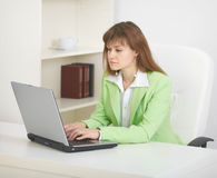 Young woman sits at table at office with laptop Royalty Free Stock Images