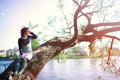 A young woman sits on a tree branch near the water and touches her hair. Spring portrait at sunset Royalty Free Stock Images
