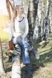 Young woman sits on a trunk of the tumbled down birch Stock Photo