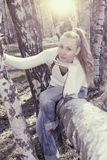 Young woman sits on a trunk of the tumbled down birch, toning Stock Photography