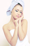 Young woman sits turned in a bedsheet Royalty Free Stock Images