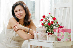 Young woman sits at a window. Young woman in a summer dress with gift boxes and roses Royalty Free Stock Images